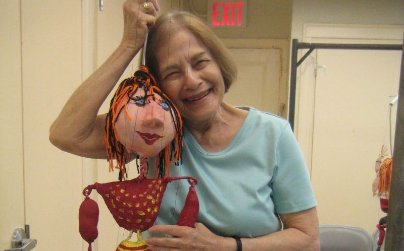 woman holding a puppet and smiling at the camera