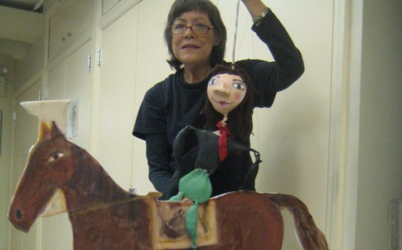 woman holding a puppet on a horse