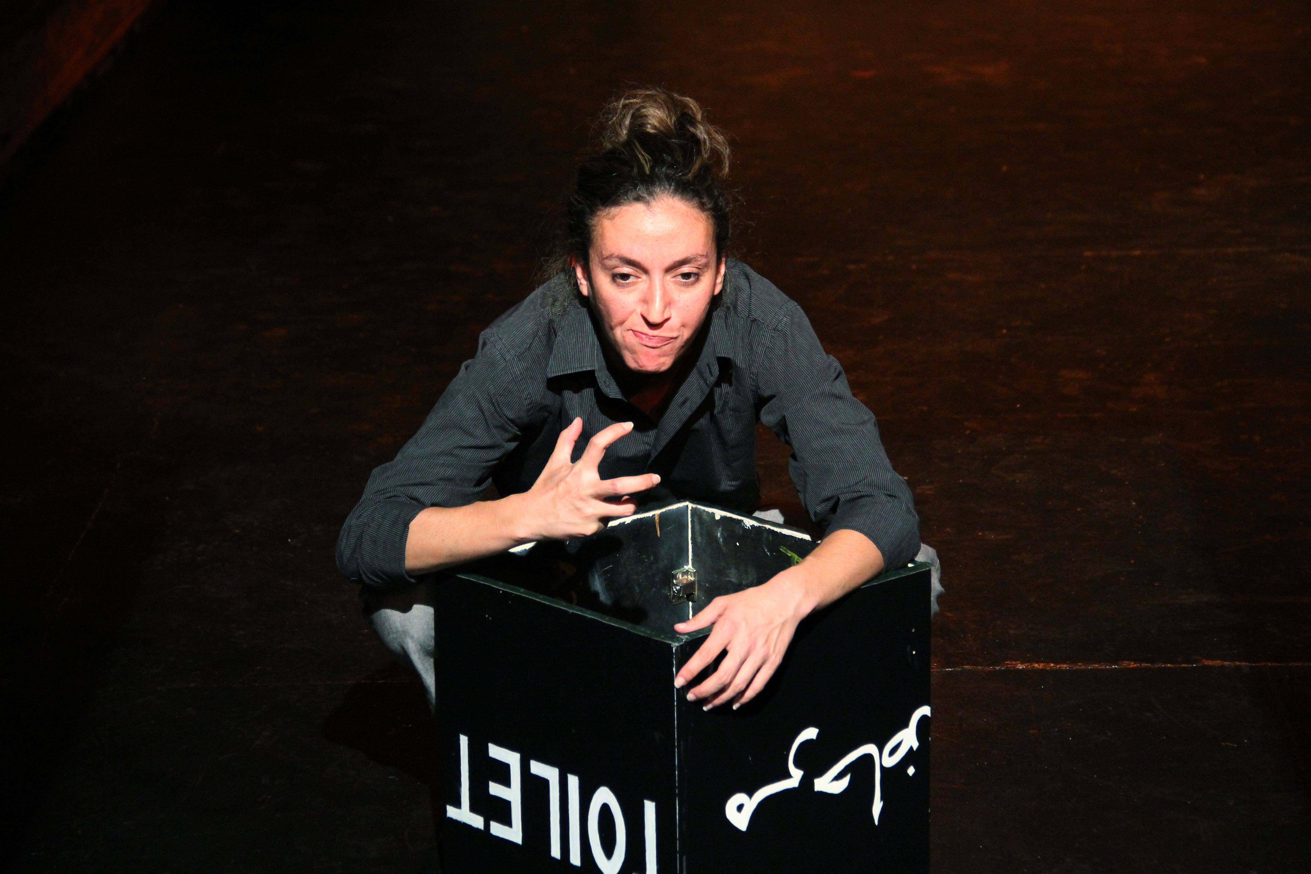 performer crouching over a box