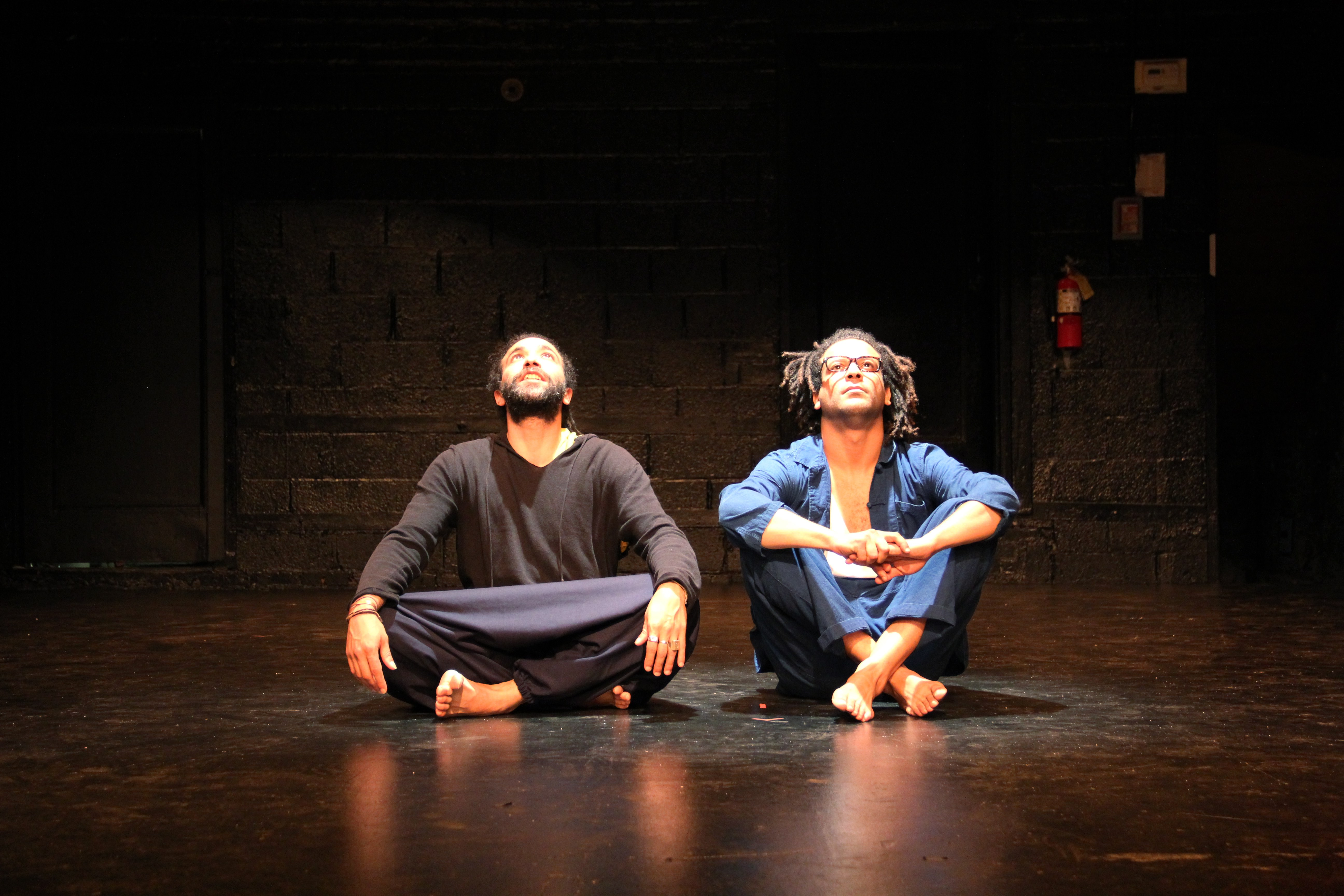 two performers sitting onstage looking up