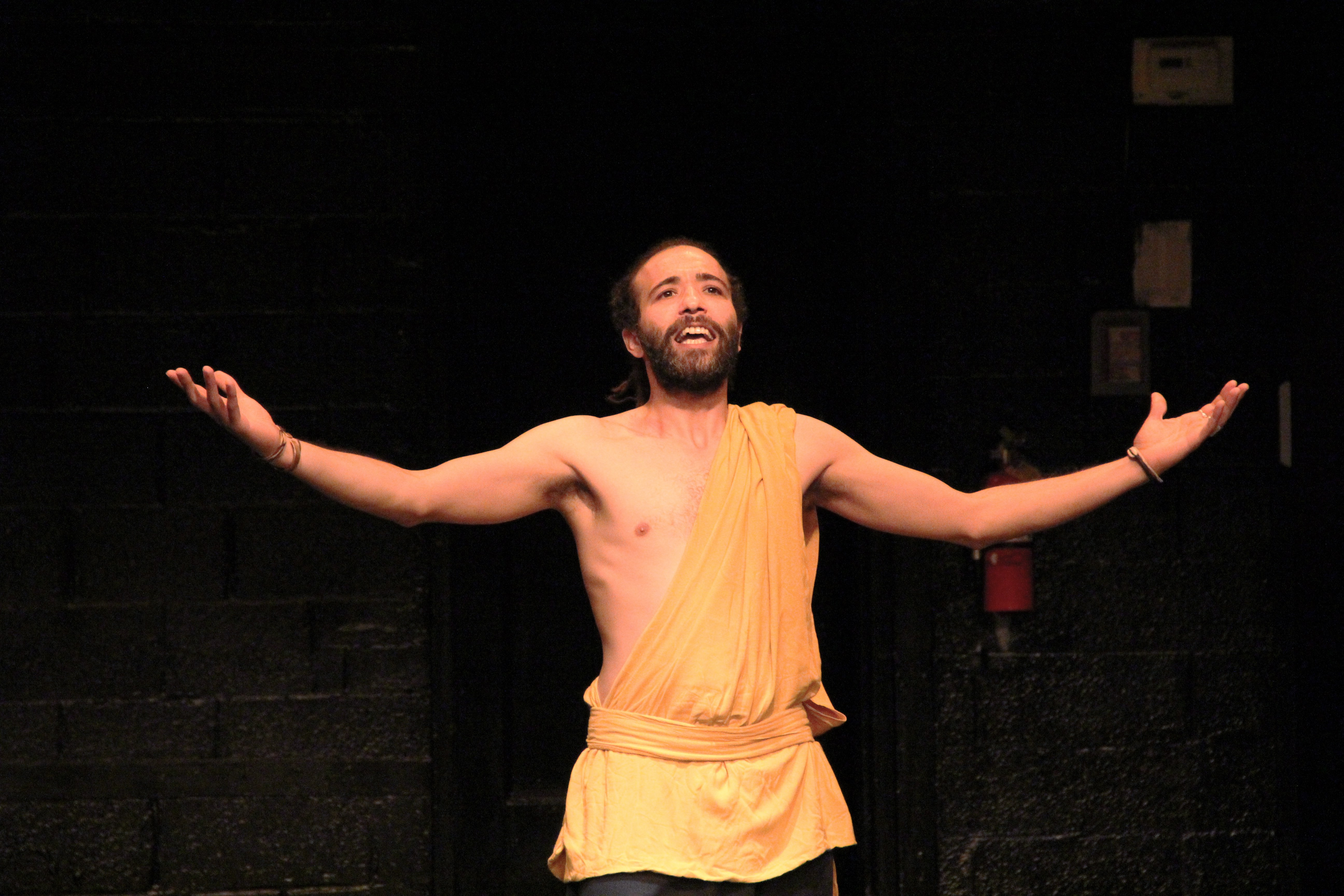 shirtless performer with arms outstretched looking up