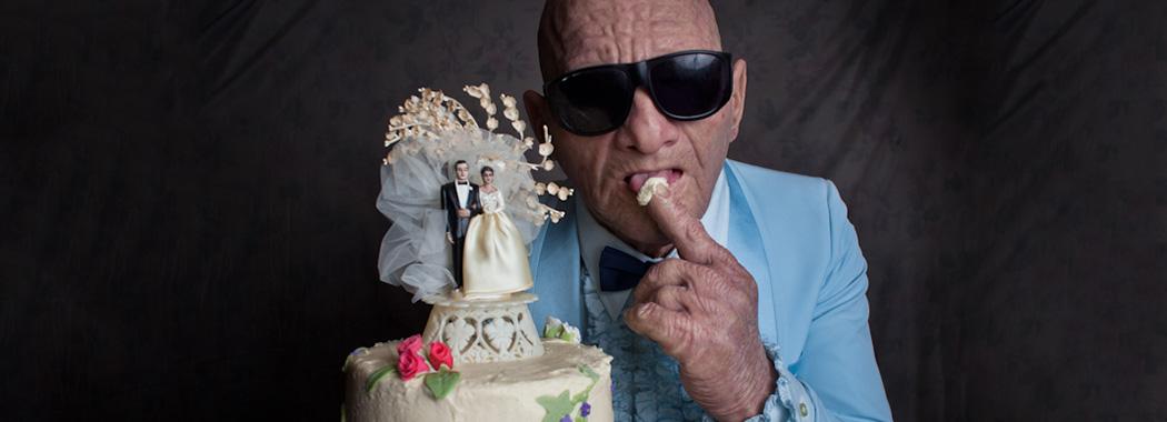 man wearing glassing holding a wedding cake