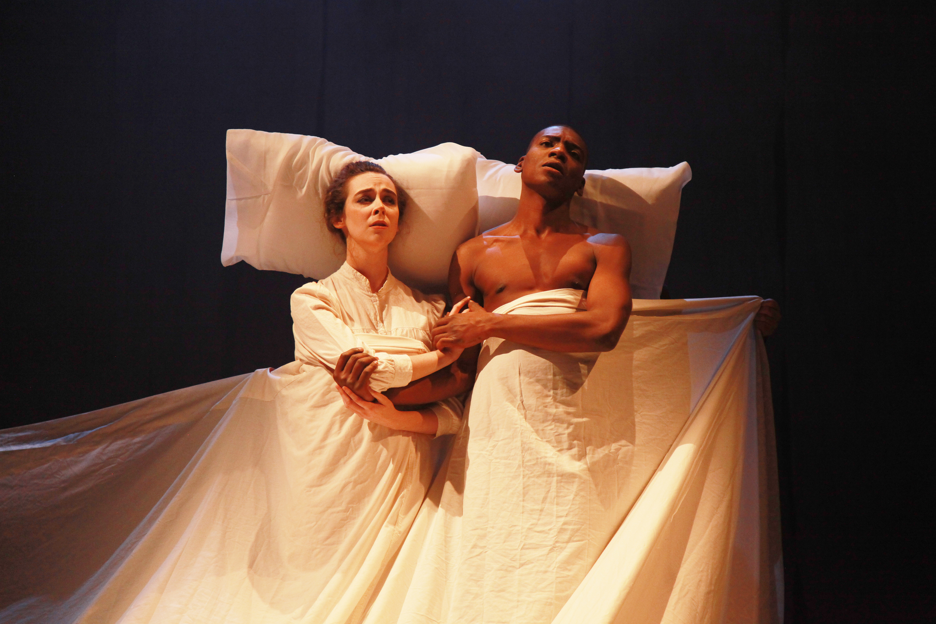 two performers laying in bed