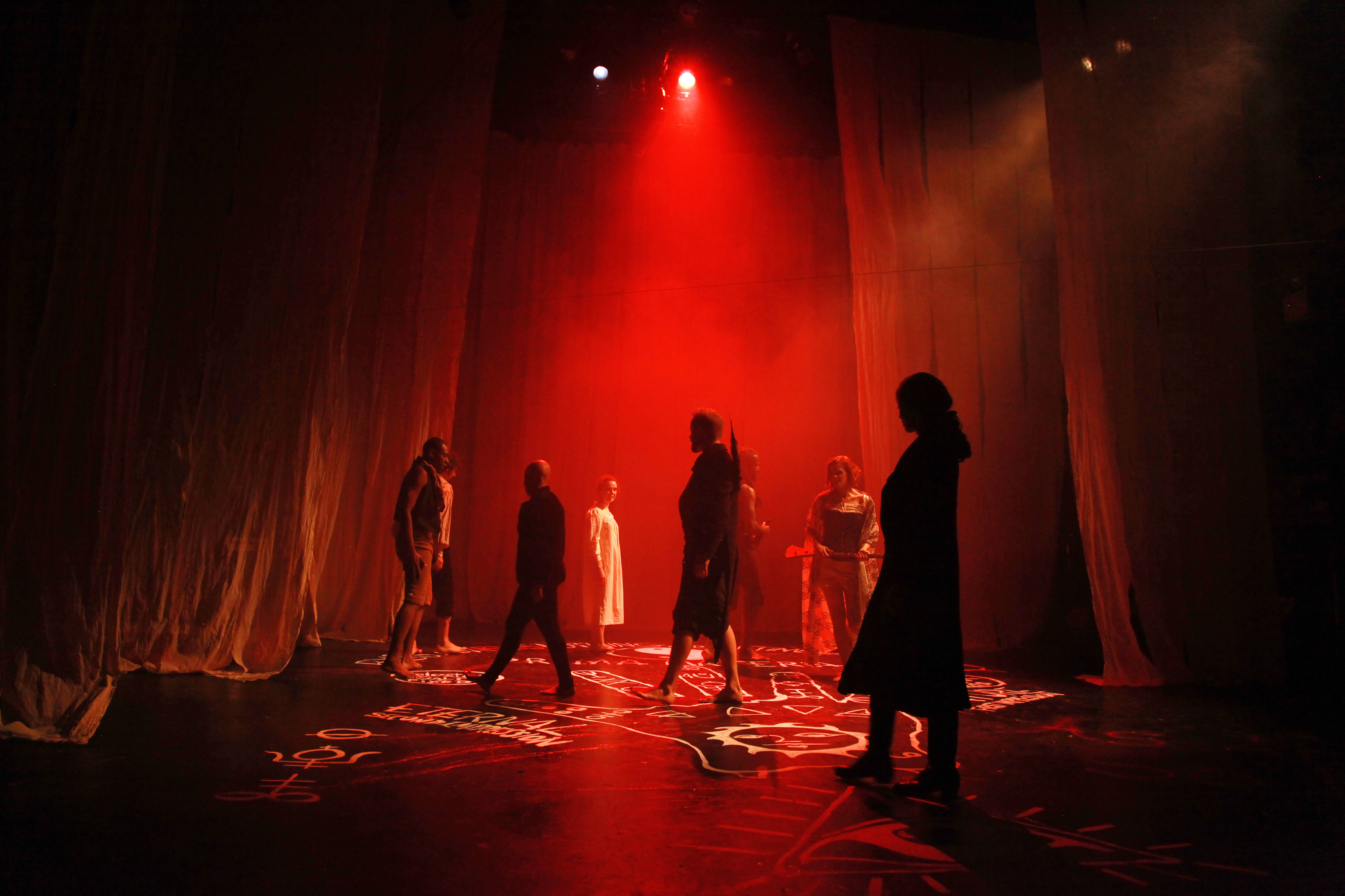 group of performers lit by red light