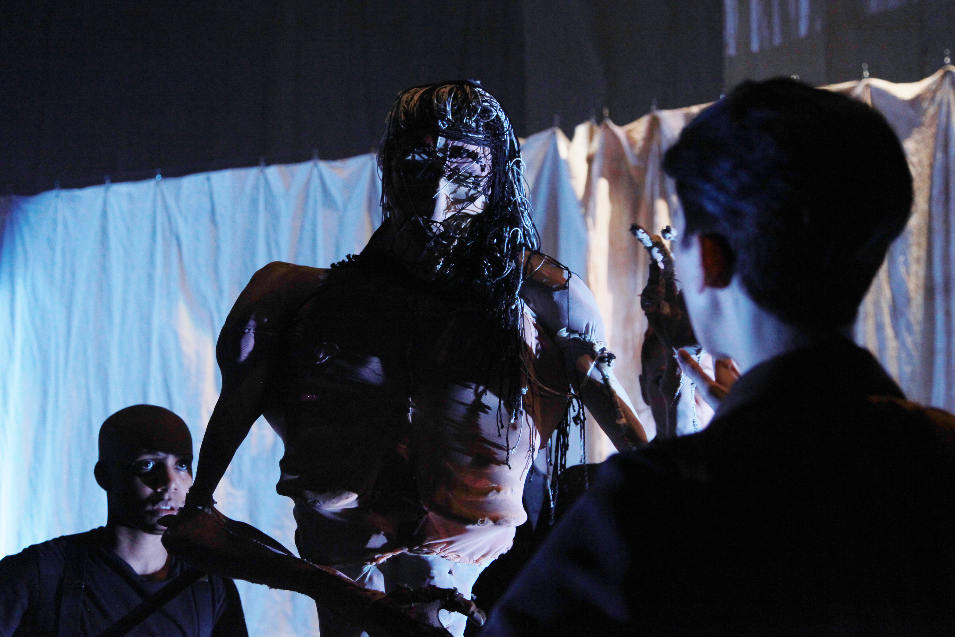 two performers looking at a human sized puppet