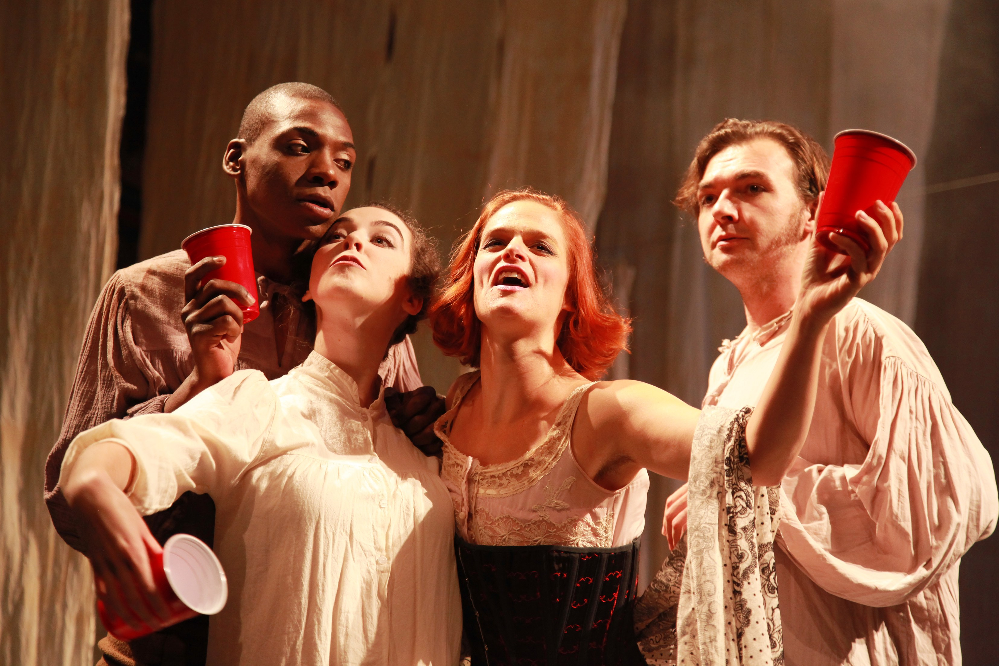 group of performers holding red cups
