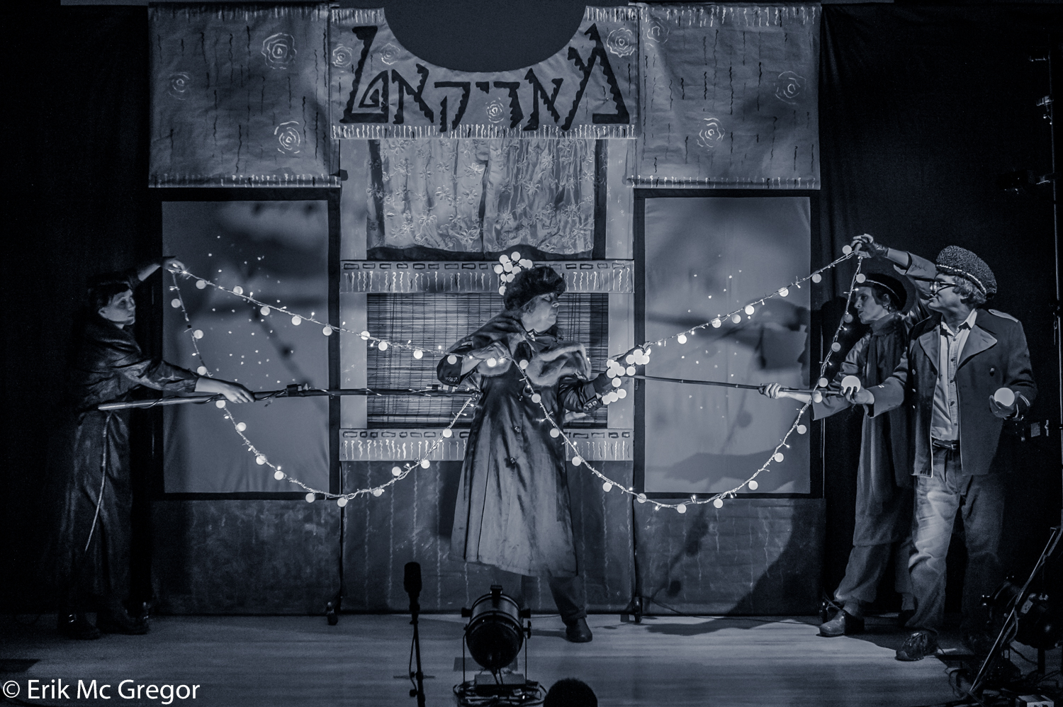 black and white photo of a performer holding string lights