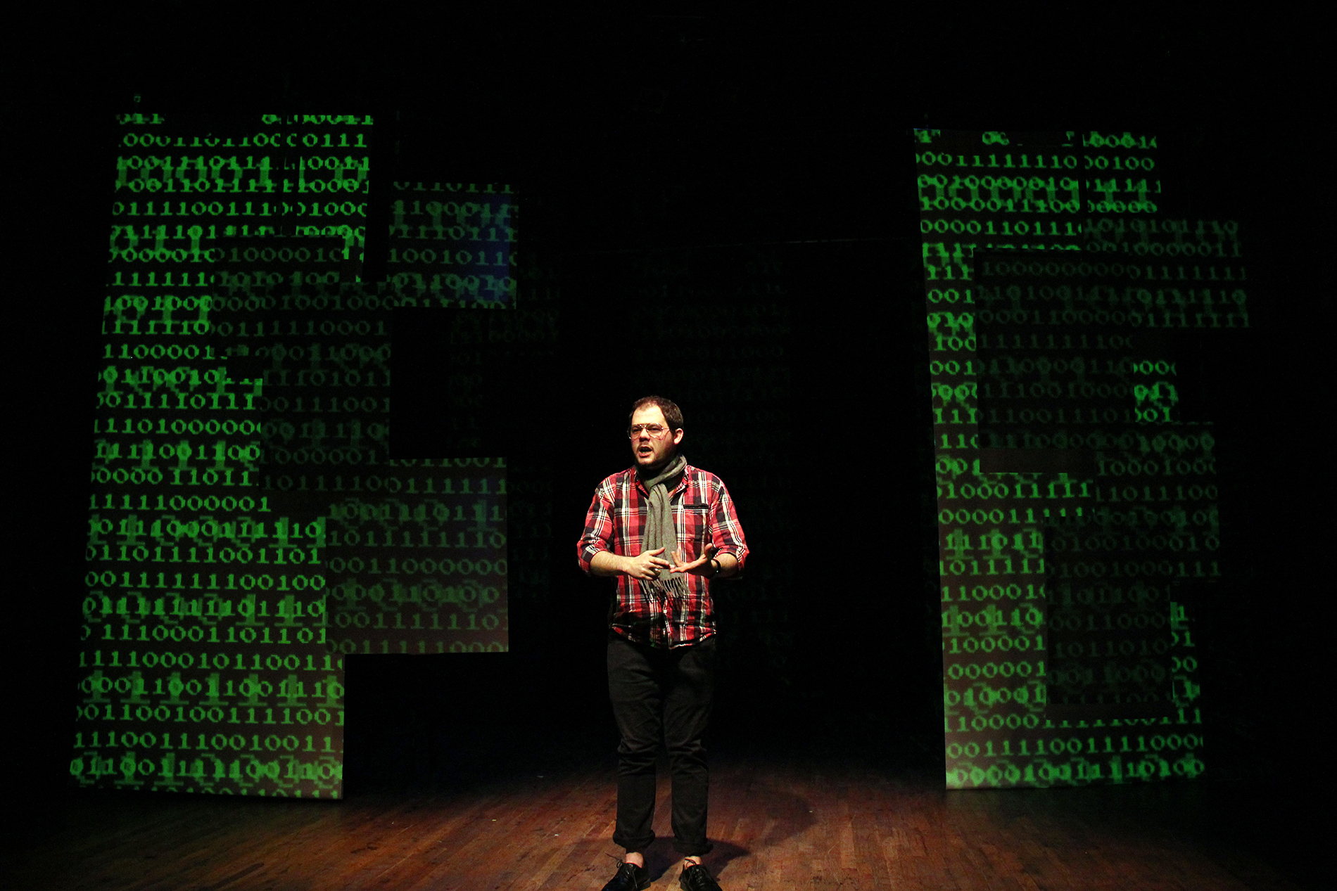 performer onstage surrounded by green code