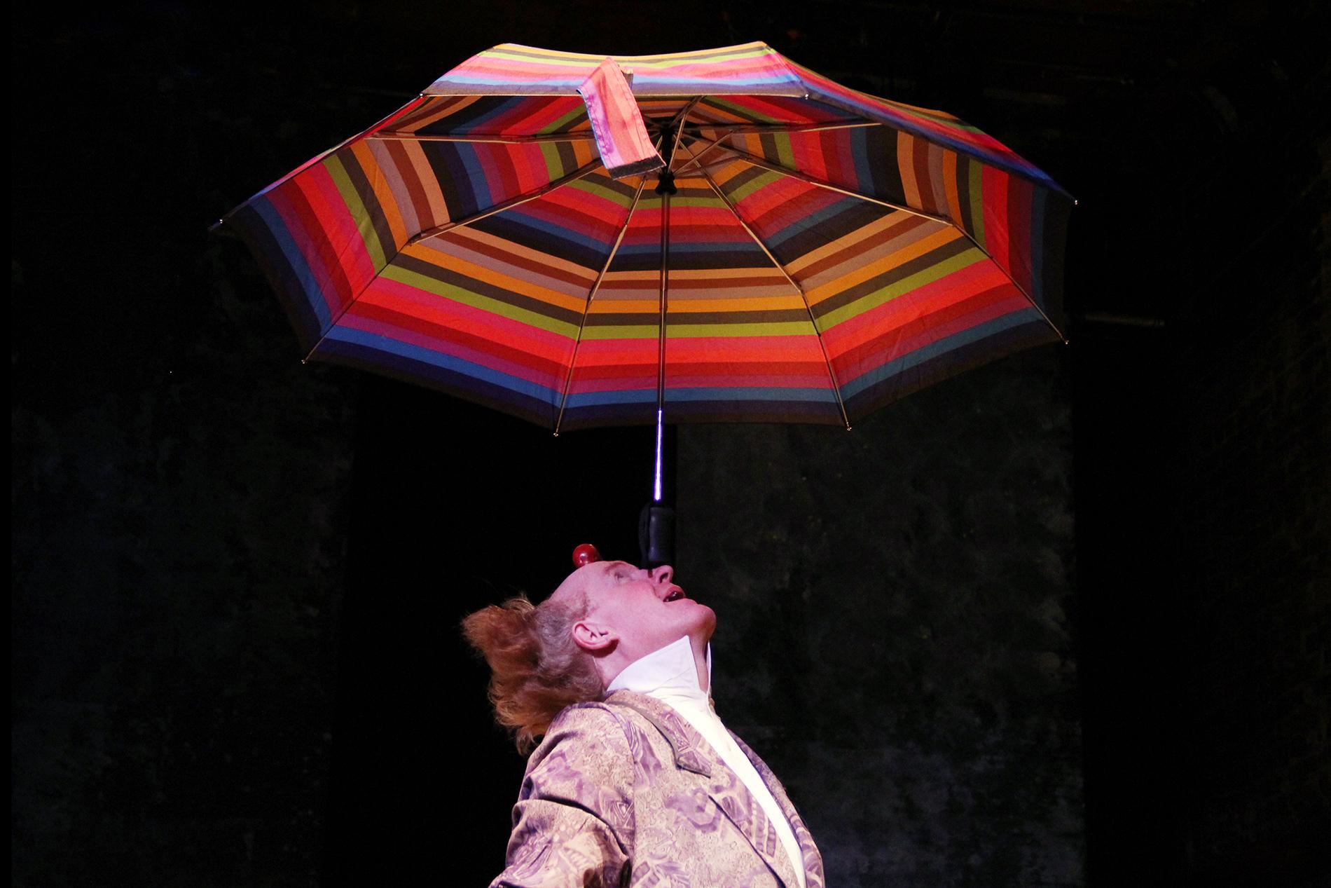 a performer balancing an umbrella on his nose