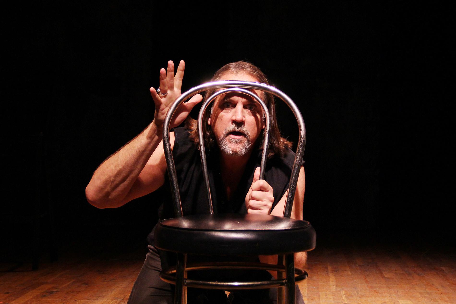 a performer crouching behind a chair