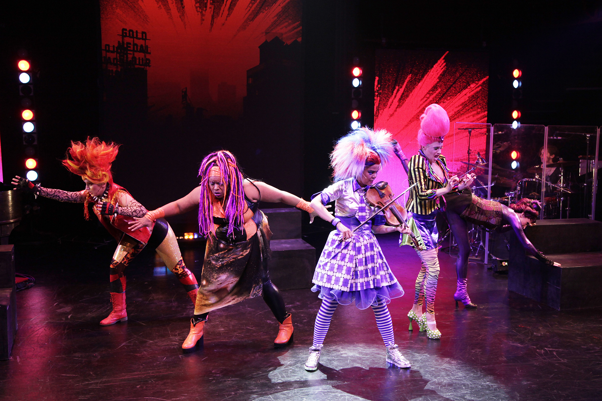 four performers in colorful costumes