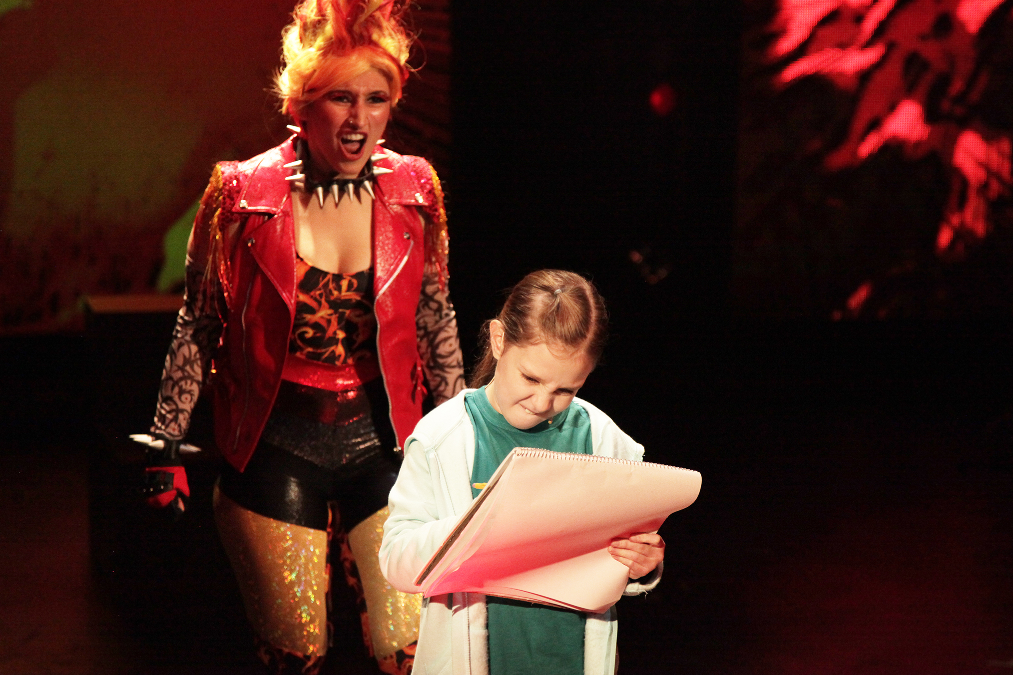 a girl writes on a piece of paper while a performer stands behind her