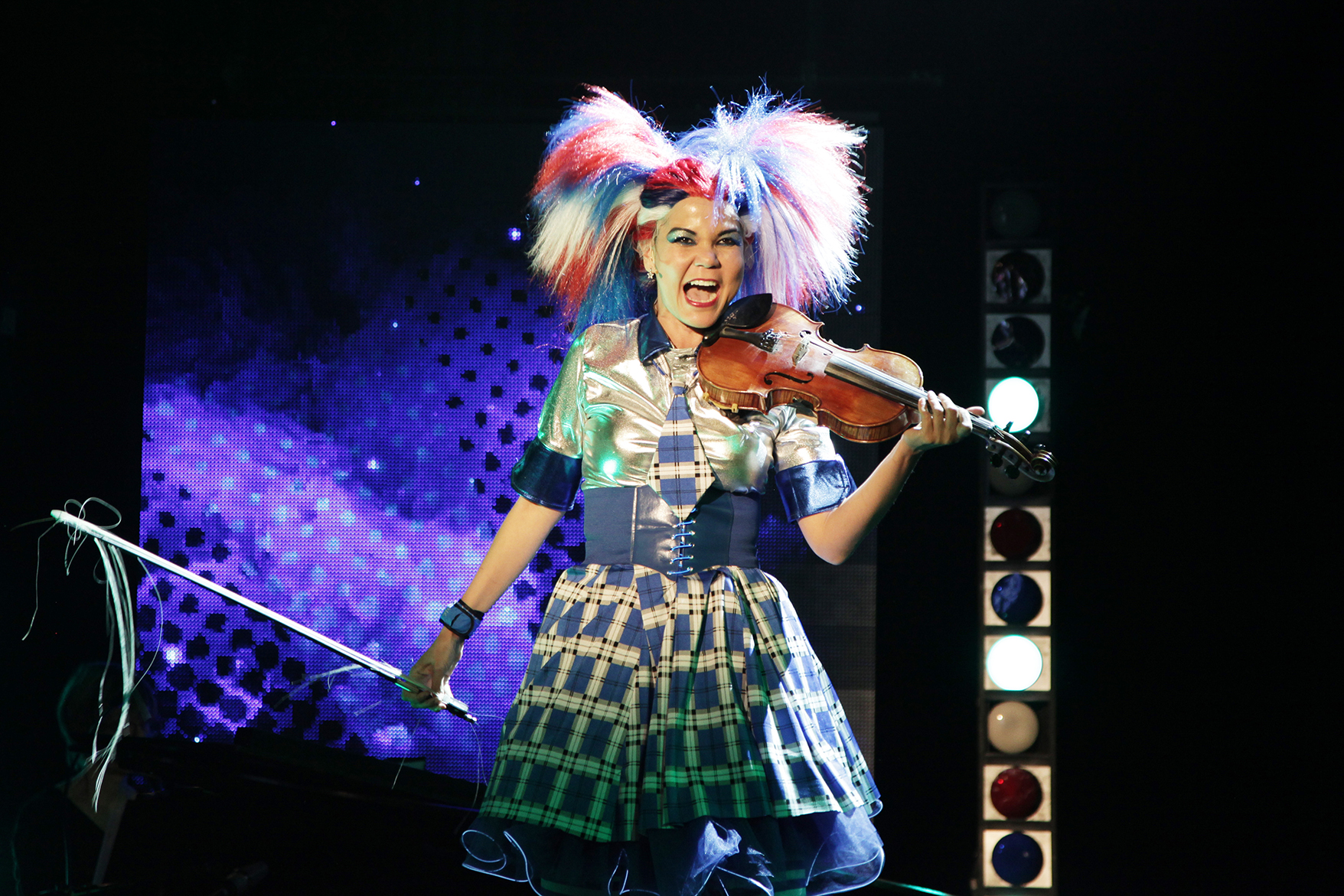 performer playing the violin in a bright wig