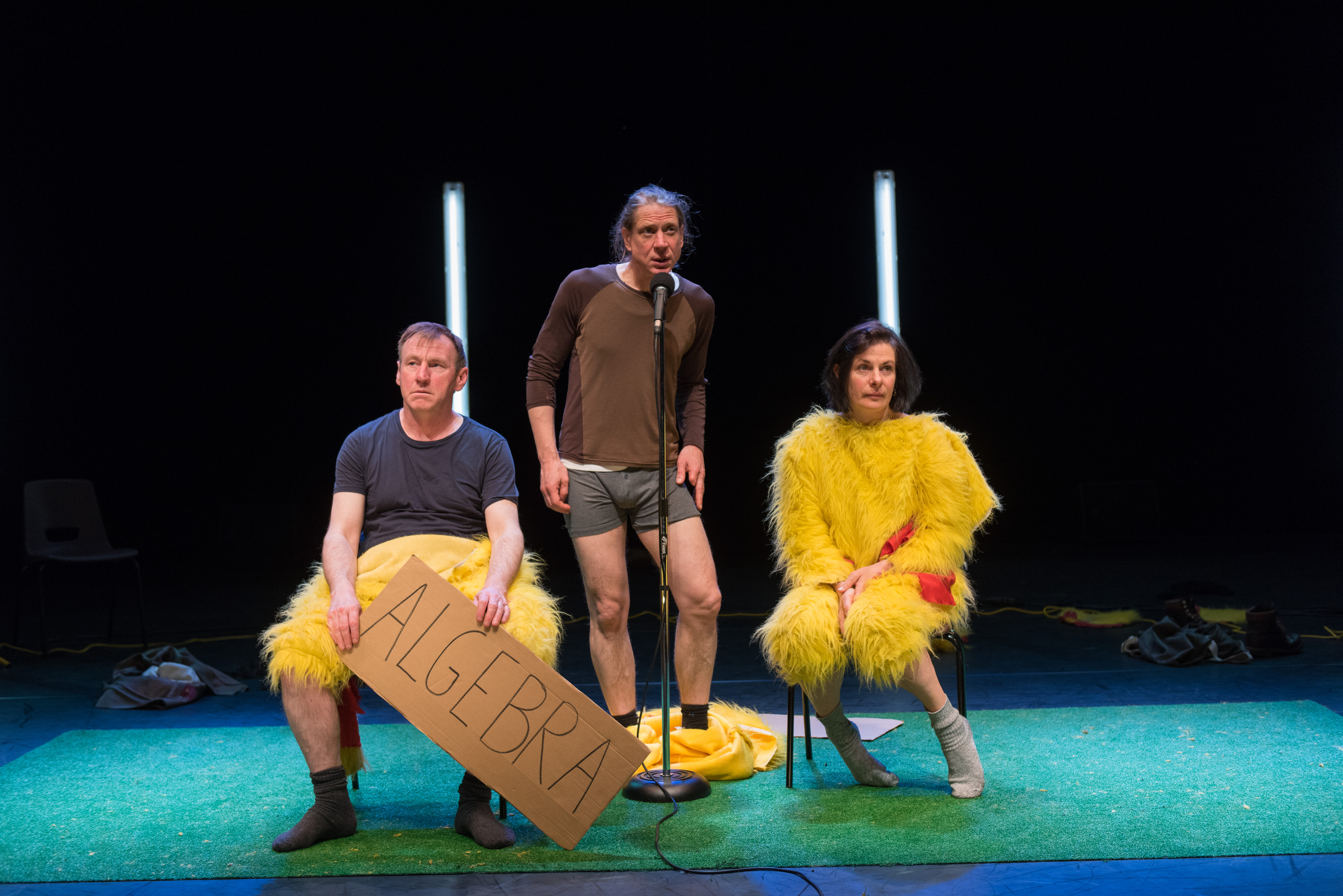 three performers onstage, one is holding a cardboard sign that says Algebra