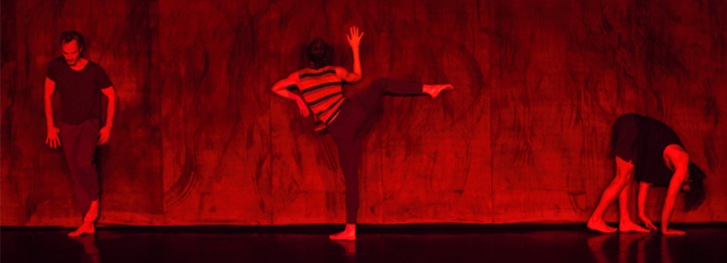 performers dancing on a wall in red light