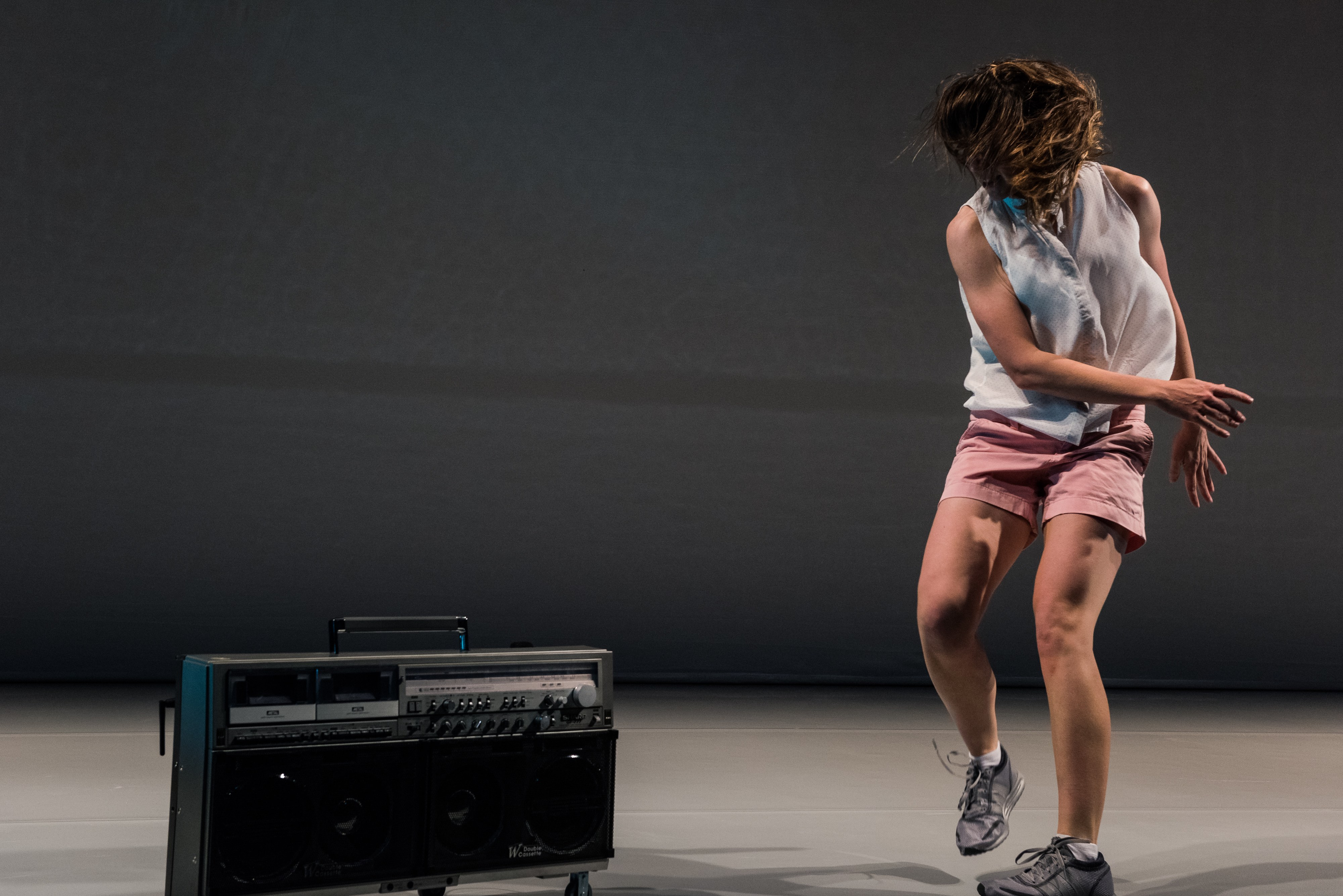 performer in white and pink dancing next to speaker