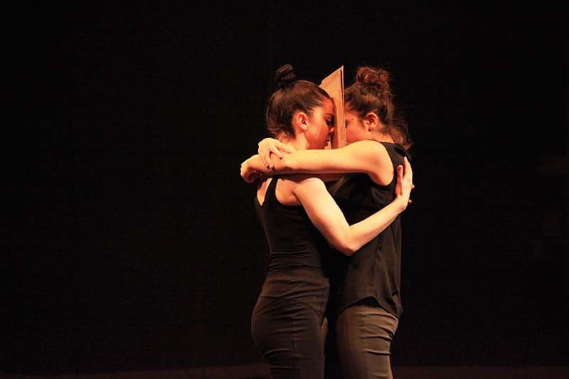 two performers embrace