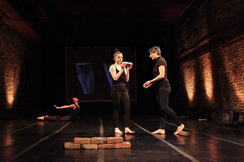 three performers standing over bricks