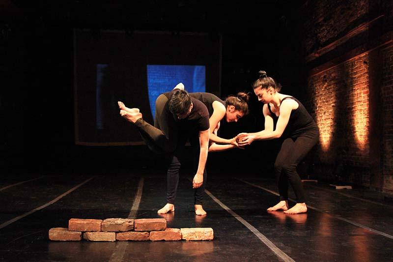 three performers dancing over bricks