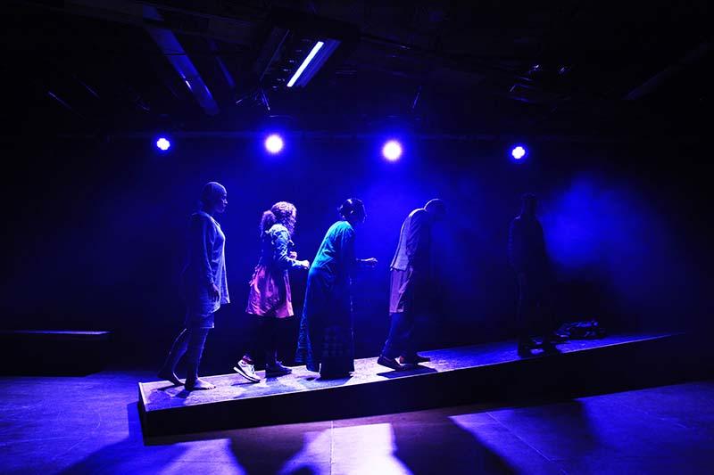fiver performer lit by purple light