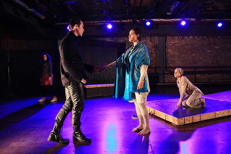 three performers lit in purple light