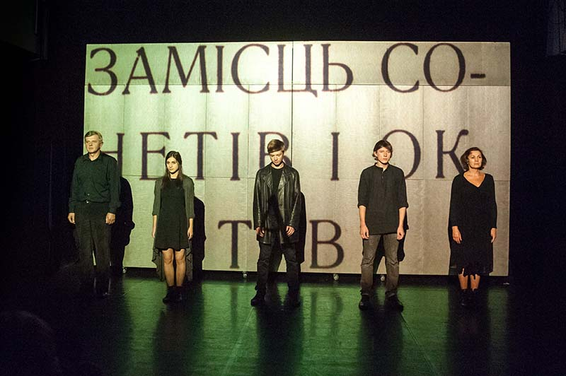 five performers standing in front of a projection