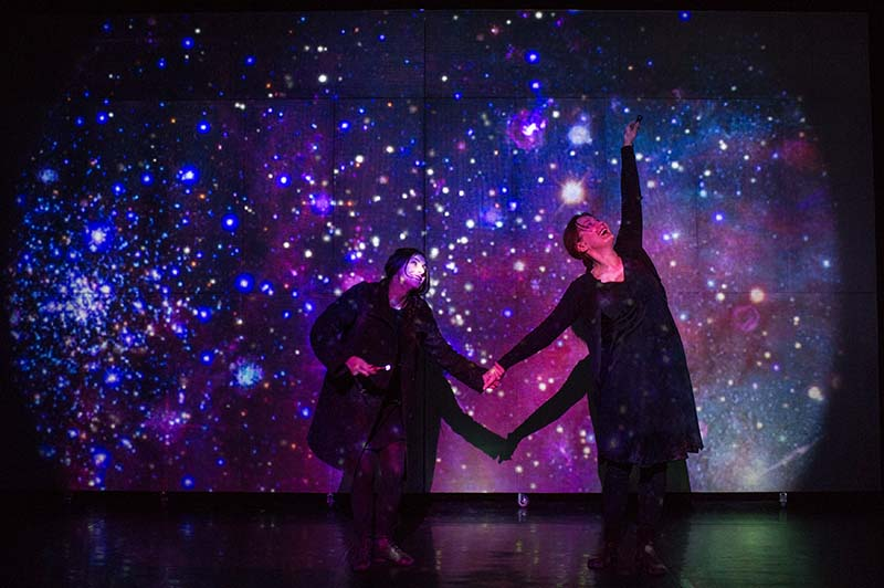 two performers in front of a projection of stars