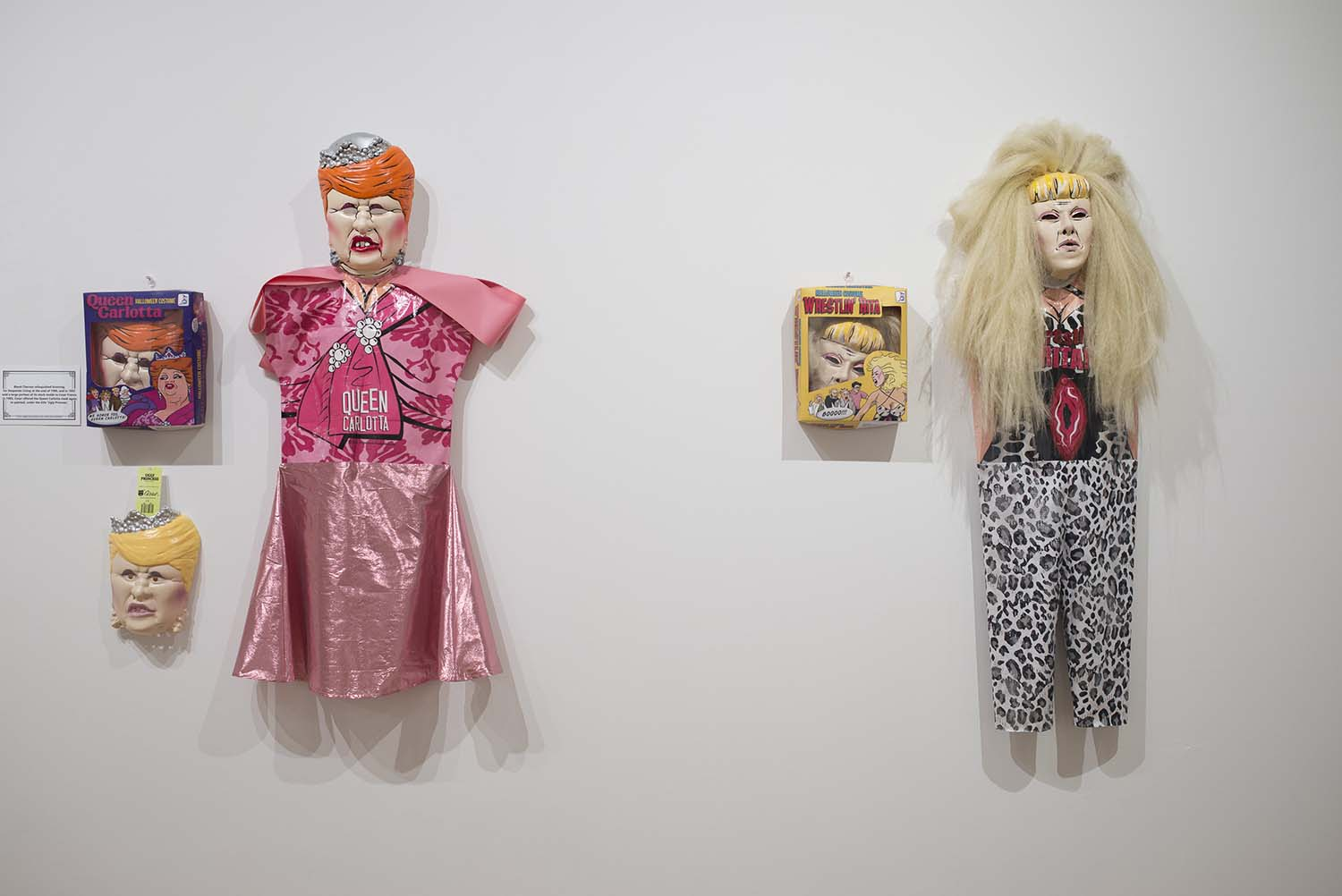 two costumes hanging in a gallery