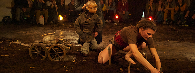 performer and a puppet on the ground