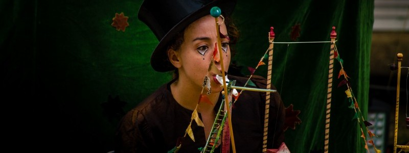 performer in a top hat in front of a flea circus