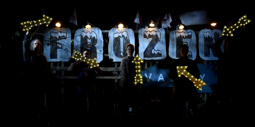 """performers holding glowing arrows in front of a sign that says """"frozen"""""""