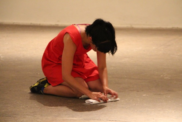performer in a red dress kneeling on the ground