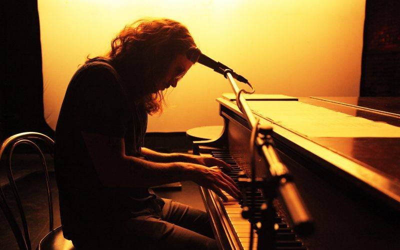 man in silhouette sitting at the piano