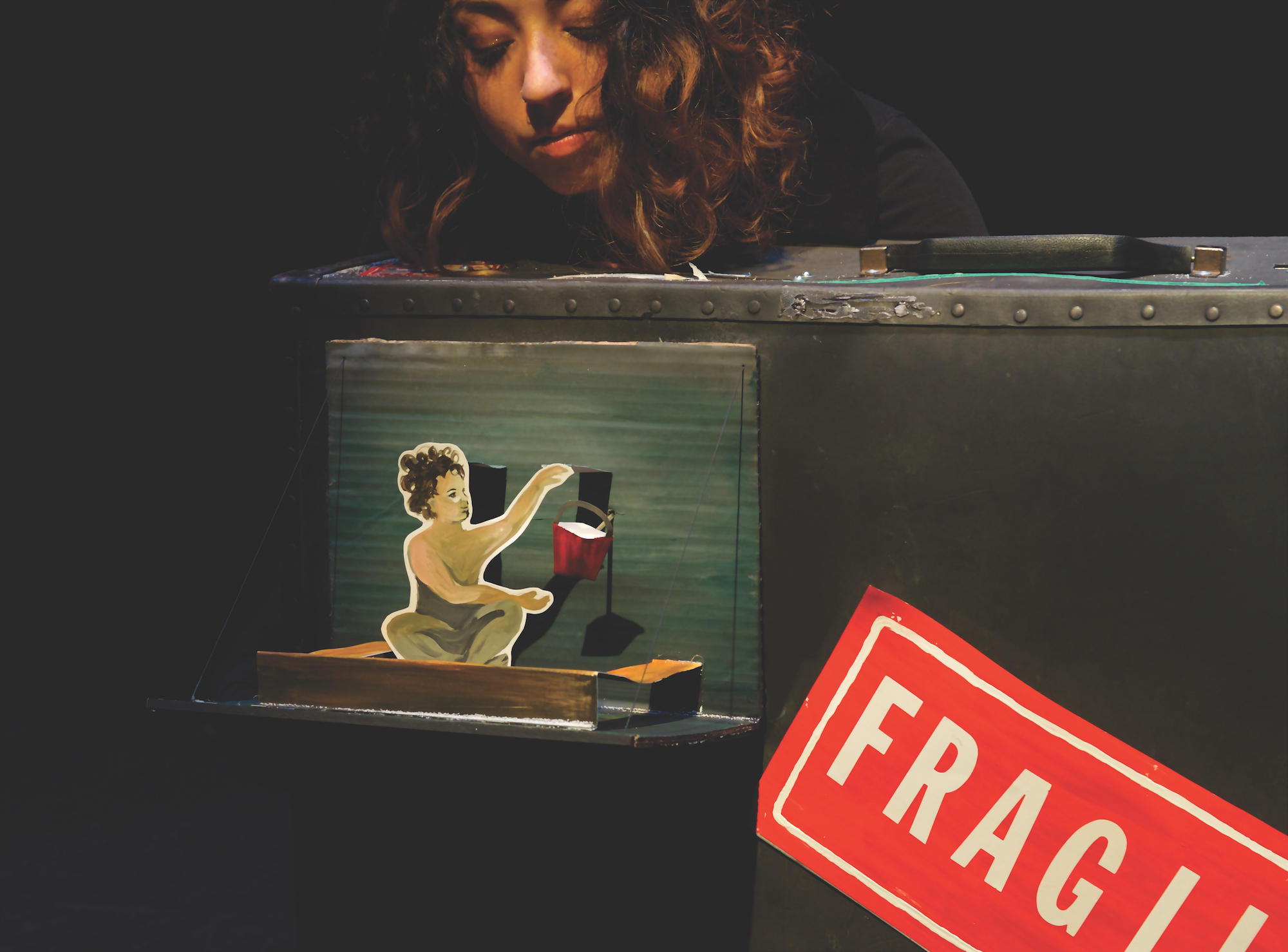 """A puppeteer is behind a large suitcase with a handle. In front is a paper cut-out of a child and a red bucket. The front of the suitcase has a big red sticker that reads """"FRAGILE"""" in white letters, with the last few letters cut off."""