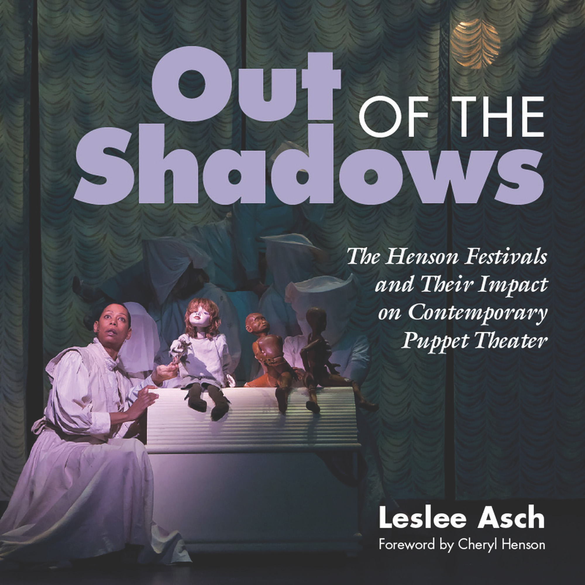 """A Black performer is on stage next to a white set piece with three puppets. The text reads """"Out of the Shadows,"""" """"The Henson Festivals and Their Impact on Contemporary Puppet Theater"""" in italics, and """"Leslie Asch, Foreward by Cheryl Henson."""""""