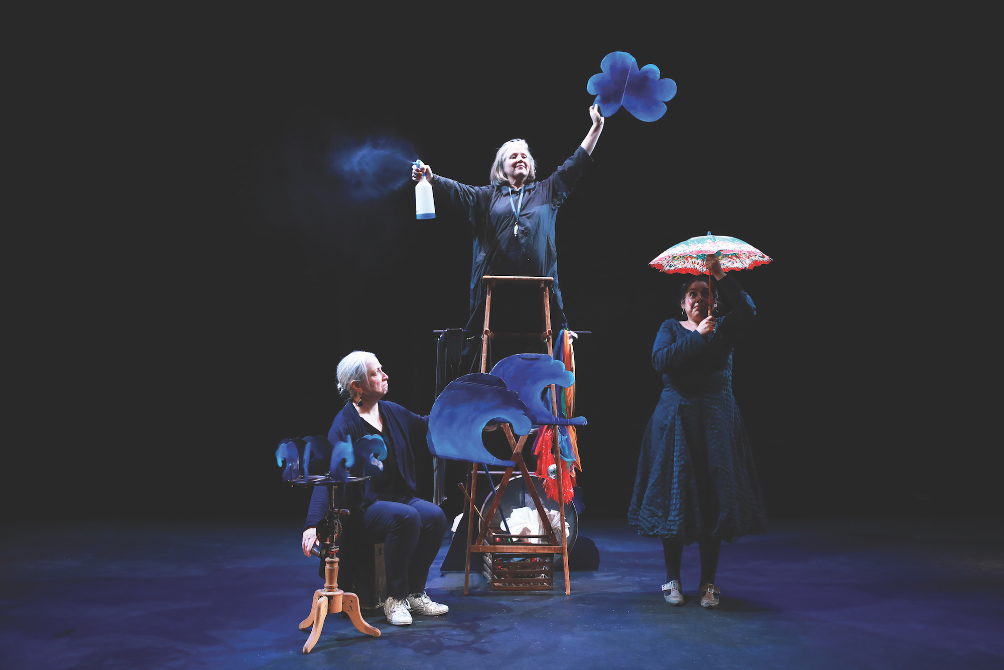The performer on the left is holding a stand and props that look like blue waves. The one in the middle is standing on a wooden ladder, holding a blue cloud and a spray bottle. The one on the right is holding a parasol over their head.