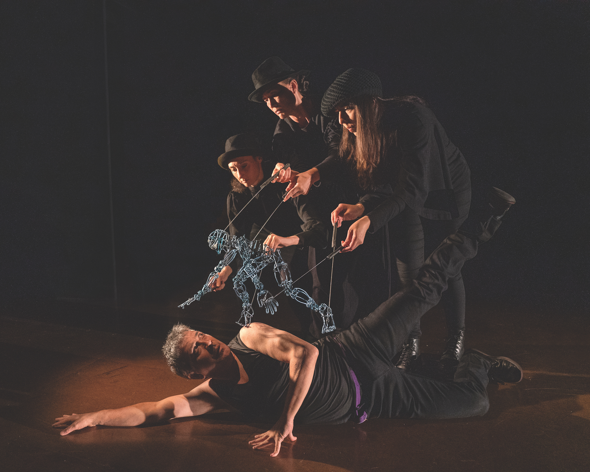A performer is lying on the floor with their hands on the floor. They are looking up at a metal human figure being controlled by three puppeteers wearing black.