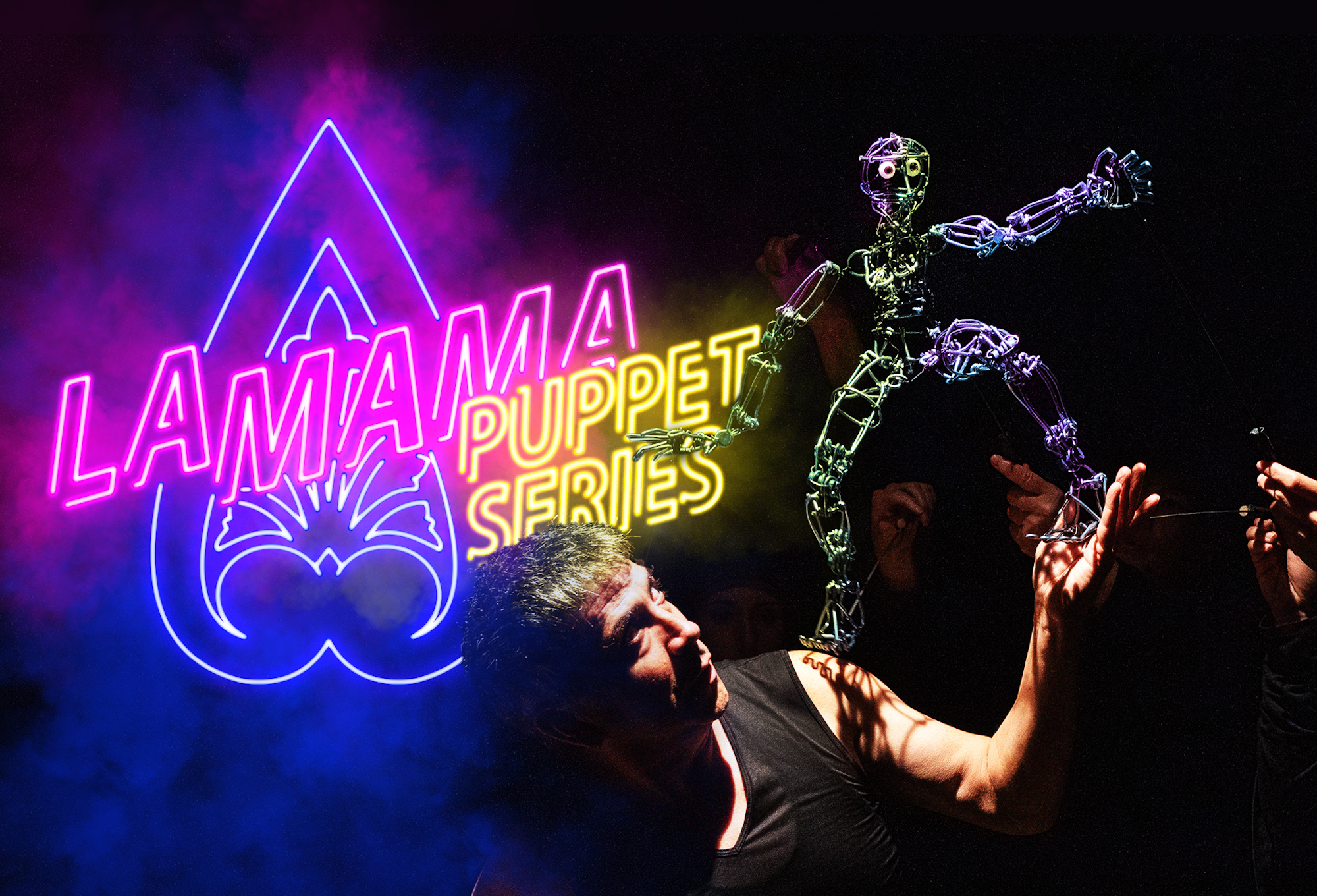 """In the background are neon lights that read """"La MaMa Puppet Series"""" in blue, pink, and yellow. A performer with short hair is wearing a black tank top and holding a metal human figure with eyes. The metal figure's right foot is on the performer's shoulder, and its left foot is on the performer's hand. There are other human hands in the background."""