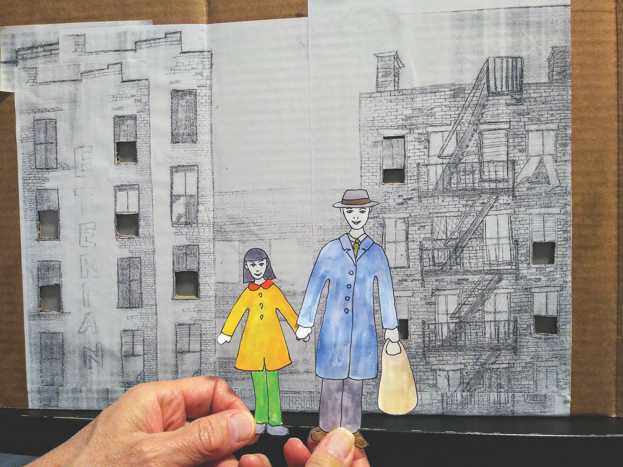 Two paper cut-outs of a man and a girl holding hands are held by two human hands. The man on the right is wearing a hat, a blue long coat, a tie, and pants, and is holding a tan bag in his left hand. The girl has dark hair, a yellow shirt with a red collar, and green pants. Behind them is a backdrop with brick buildings drawn in pencil.