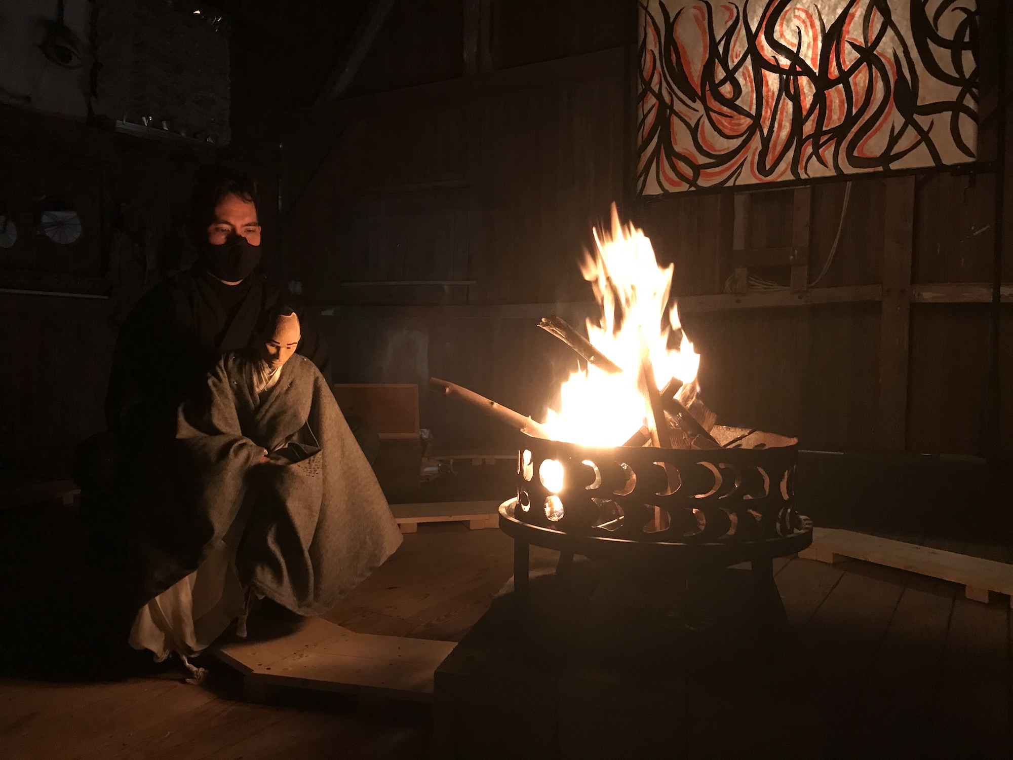 A puppeteer with dark hair and a black mask is holding a puppet wearing a kimono. To the right of them is a fire with burning wood in it. In the background is a painting with black and red strokes.