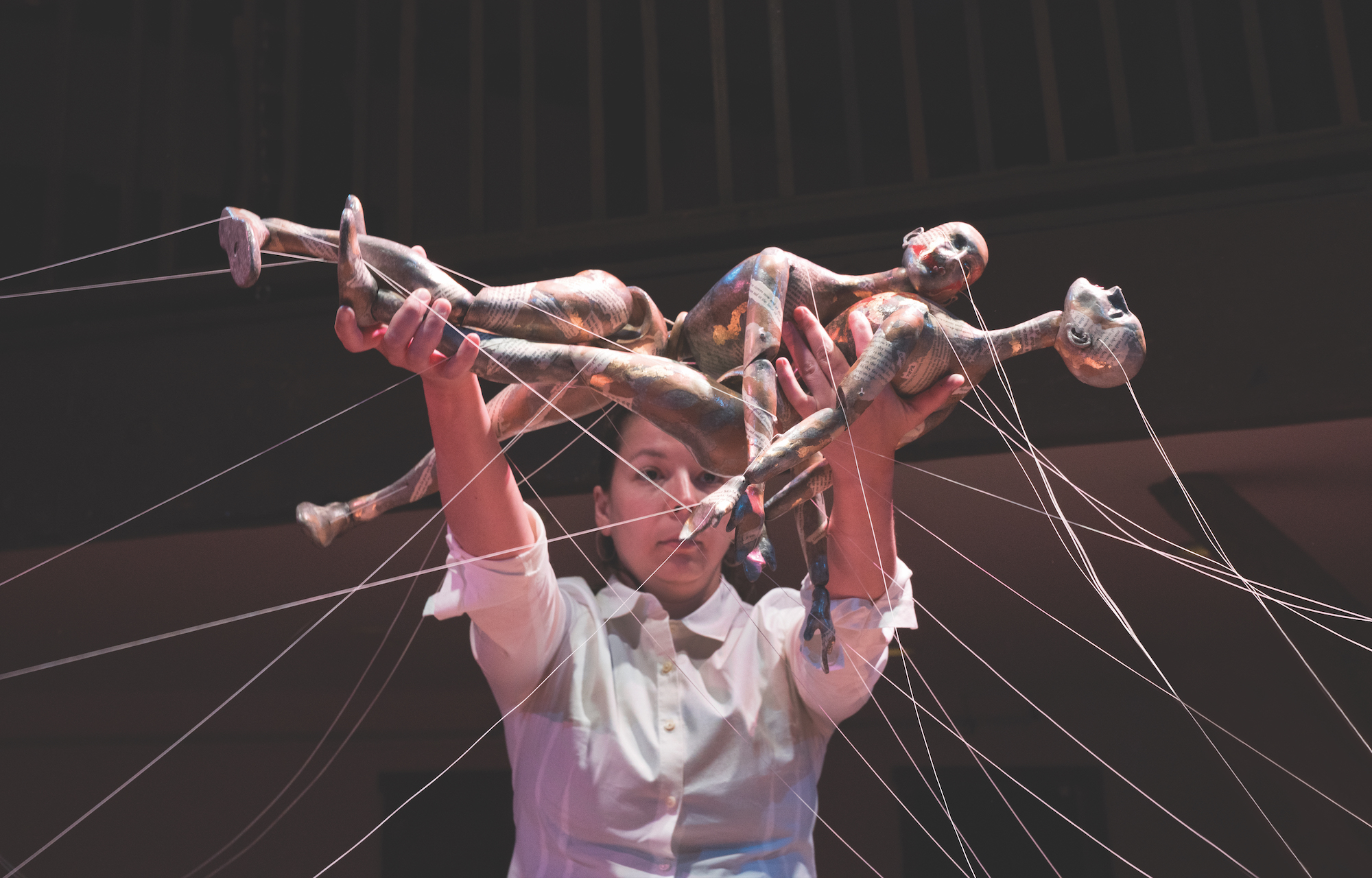 A puppeteer in a white shirt is holding two human figures. One is lying on top of the other. There are many white strings connected at various points on the figures and continuing out of the frame.