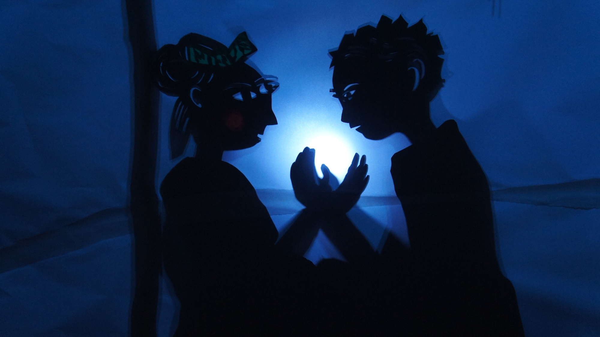 Two shadow puppets are in front of a blue background with a light in the center. Two hands are cradling the light, and the eyes of both shadow puppets are looking towards it.
