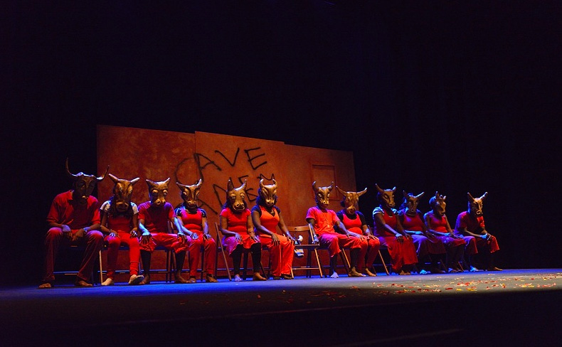 line of performers in red robes and masks