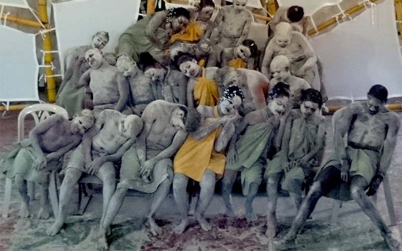 group of performers with gray ash covering their bodies