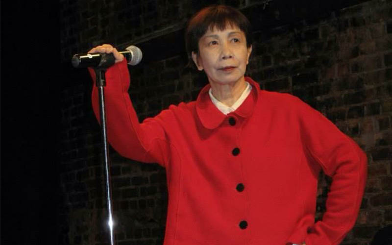 woman in red jacket next to a microphone