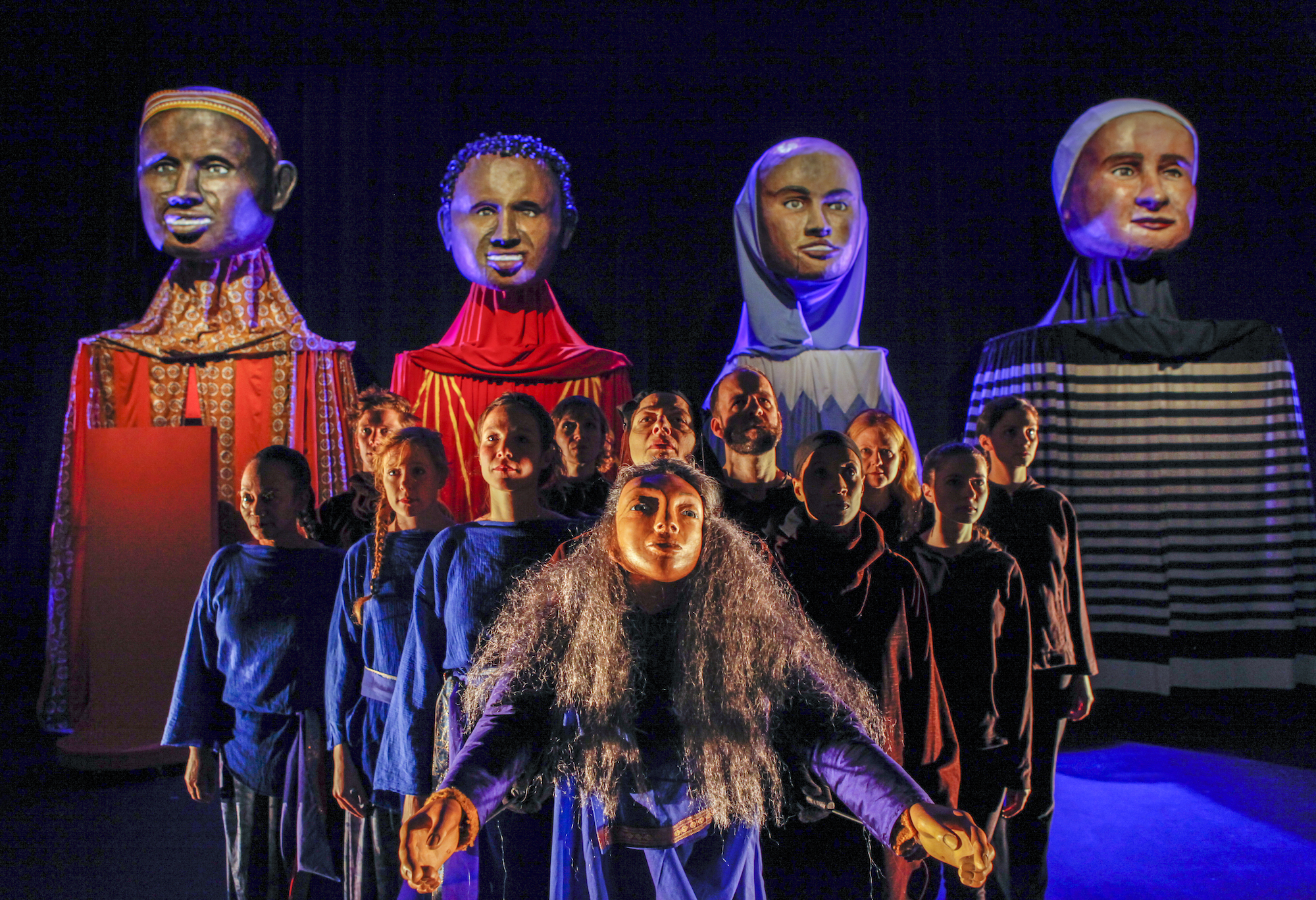 On stage, one puppet front and center has its arms outstretched. Behind it, 11 performers are gathered together and looking upwards. In the background are four large busts on top of pedestals.