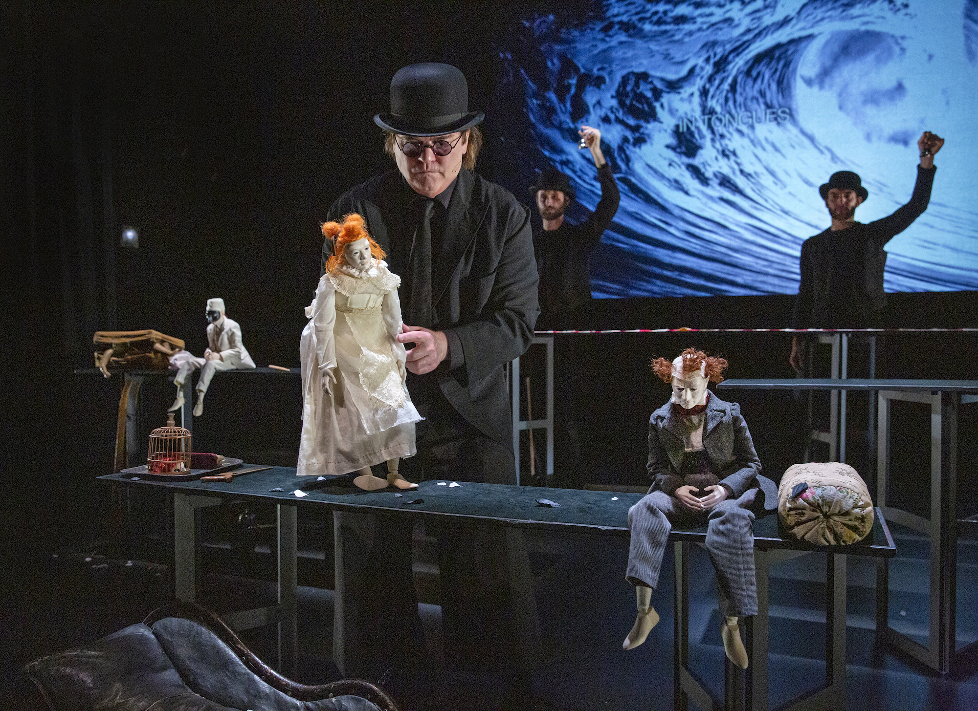 A puppeteer in a bowler hat and black suit is holding a puppet in a white dress with orange hair. There are two other puppets seated on tables. Behind them are two performers holding up objects in their left hands. The background is a projected photo of a wave.