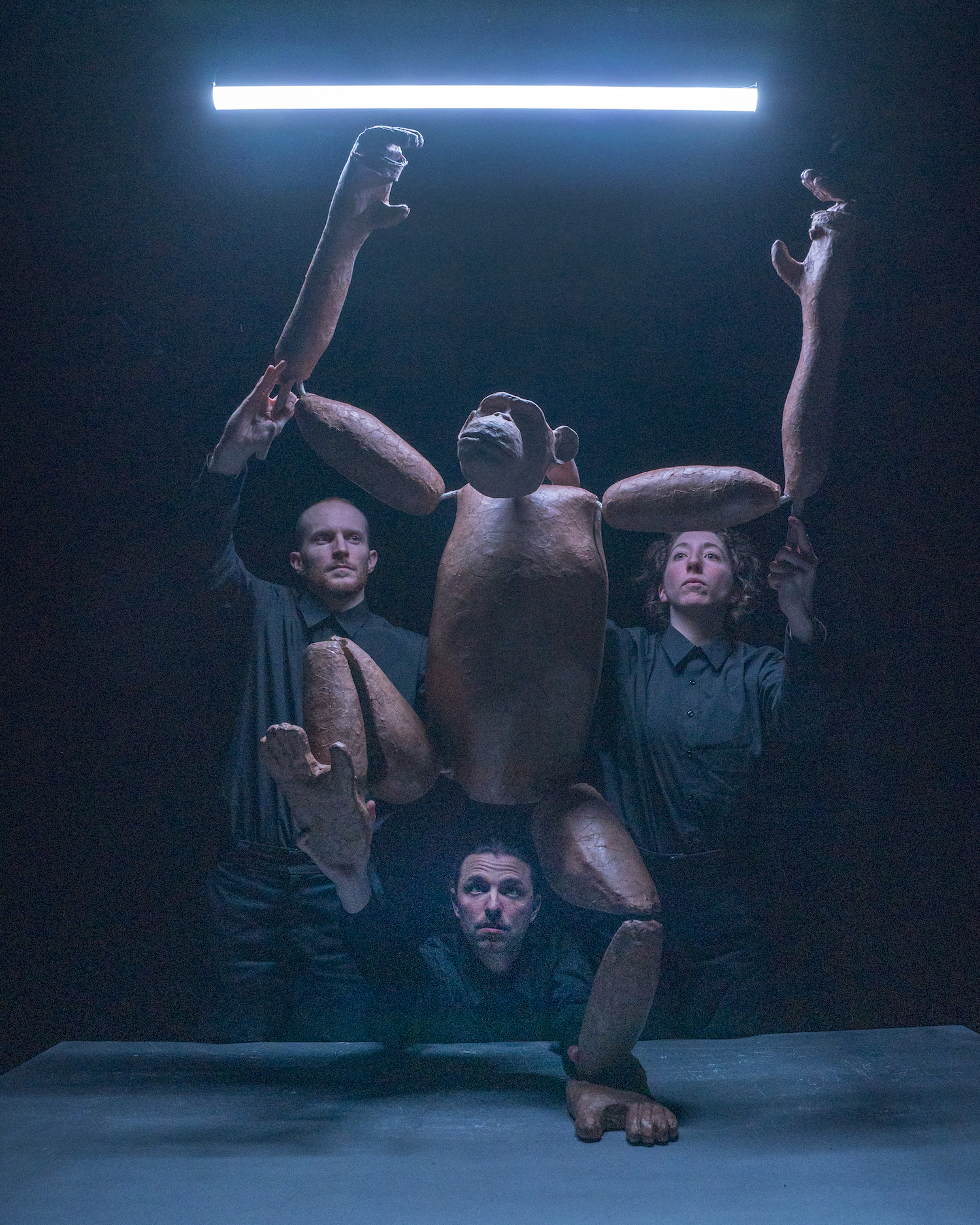 Three puppeteers are looking upwards and holding a puppet shaped like a chimpanzee. There is a tube light above them illuminating the scene.