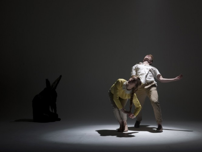 two performers dancing in a spotlight