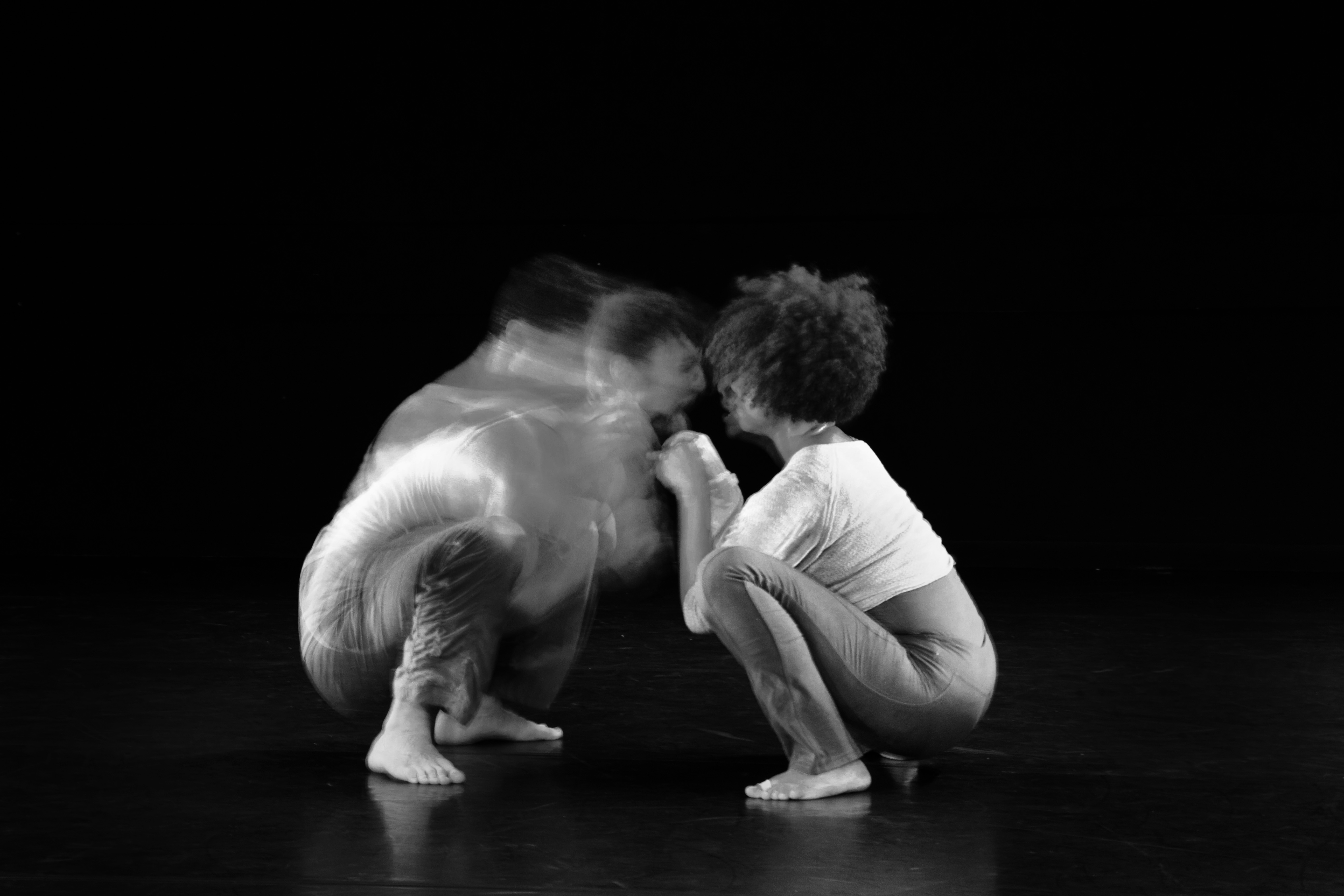 two performers crouching
